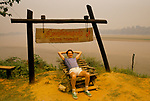Western tourist sitting under Golden Triangle sign Thailand.Mekong river border between Thailand and Laos 1990s