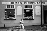 South Elmsall, Yorkshire. 1979<br /> Hemco Fireplaces, Please Walk In. A shopkeeper does her knitting minding her bric-a-brac shop sitting outside in the afternoon sun.