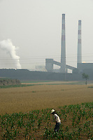 A farmer works in front of a Coking factory in Xiaoyi, Shanxi, China. Xiaoyi is reportedly one of the most polluted cities in Shanxi province. According to the first-quarter report of the State Environmental Protection Administration (SEPA), pollution across the country has been worsening and foul air emissions are beyond acceptable limits. Pollution index in some cities is above 300. Worsening air and water pollution made cancer the top killer in China last year..06 Jun 2007