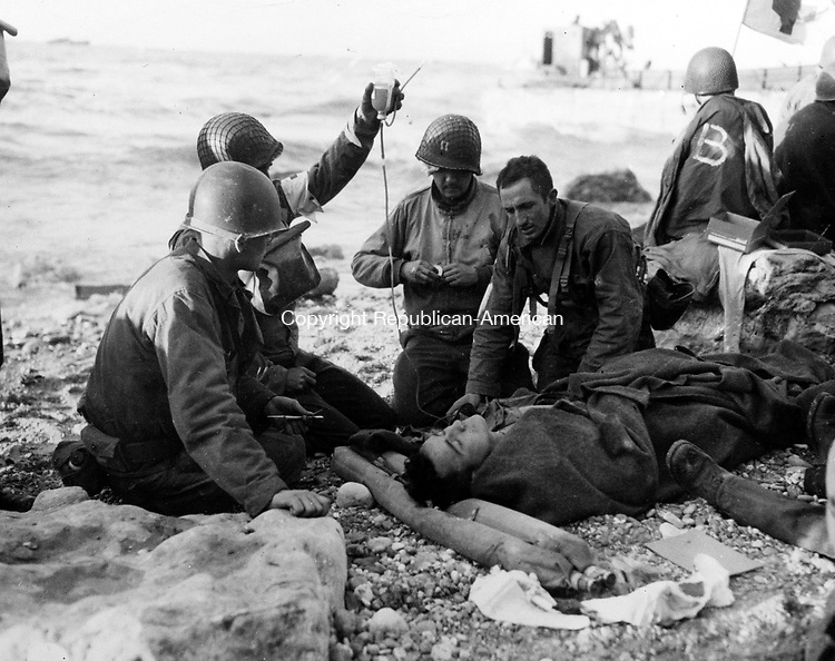 U.S. Army medical personnel administer a plasma transfusion to a wounded comrade, who survived when his landing craft went down off the coast of Normandy, France, in the early days of the Allied landing operations in June 1944. (AP Photo)