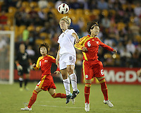 Lori Lindsey #11 of the USA WNT heads the ball away from Na Zhang #6 of the PRC WNT during an international friendly match at KSU Soccer Stadium, on October 2 2010 in Kennesaw, Georgia. USA won 2-1.