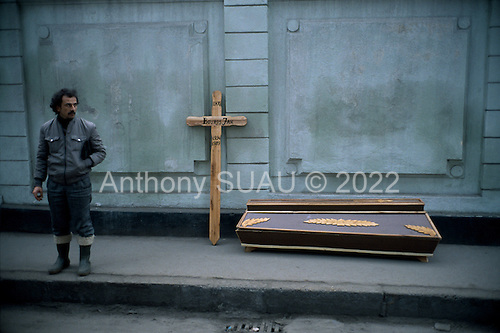 """Bucharest, Romania<br /> December 24, 1989<br /> <br /> A victim of the revolution is collected by his brother who was killed in the uprising overthrowing former leader Nicolae Ceausescu.<br /> <br /> The week-long series of violence that overthrew the Communist regime of Nicolae Ceausescu, ended in a trial and execution of Ceausescu and his wife Elena by firing squad. Romania was the only Eastern Bloc country to violently overthrow its Communist regime or to execute its leaders.<br /> <br /> The Romanian populace was dissatisfied with the Communist regime and leader Ceausescu's economic and development policies were blamed for the country's shortages and widespread poverty. The powerful secret police (Securitate) controlled what was essentially a police state. Ceausescu was not pro-Soviet but """"independent"""" on foreign policy. He imitated the hard-line, megalomania, and personality cults of communist leaders like North Korea's Kim Il Sung."""