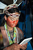 A Pataxo participant uses a smart phone during the opening ceremony at the International Indigenous Games in Brazil. 23rd October 2015
