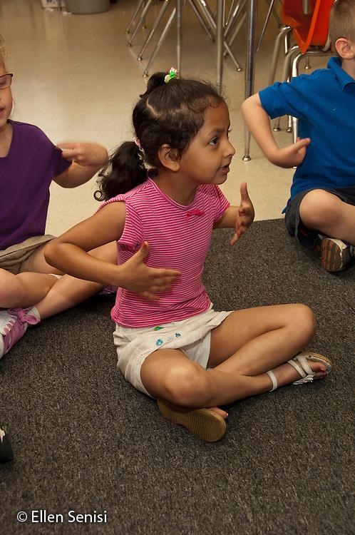 MR / Schenectady, New York. Elmer Avenue School (urban public elementary school). Kindergarten classroom. Student (girl, age 5) uses hand motions as students sing together in class. MR: Des1. ID: AH-gKg. ©Ellen B. Senisi