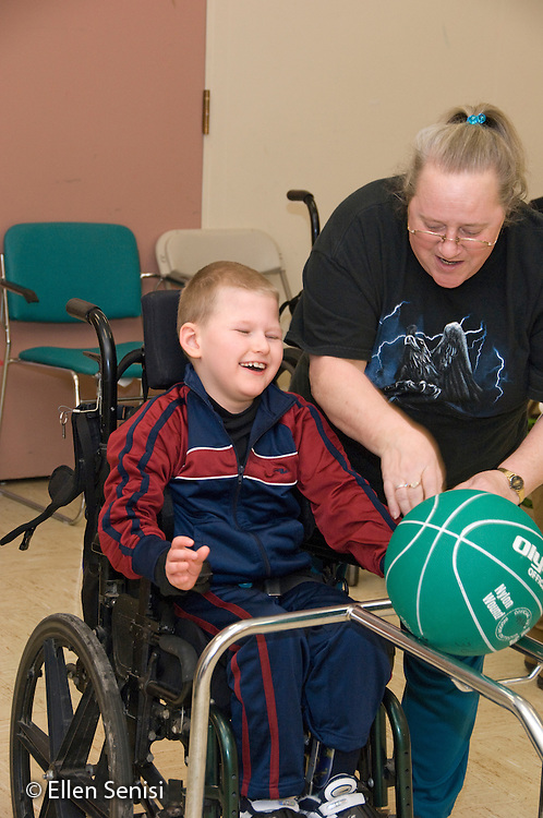 MR / Albany, NY.Langan School at Center for Disability Services .Ungraded private school which serves individuals with multiple disabilities.Teaching assistant is giving directions and encouraging student to push ball down ramp in Adaptive Physical Education class (APE). Boy: 9, cerebral palsy, non verbal with expressive and receptive language delays.MR: Law4, Par10.© Ellen B. Senisi