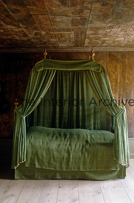 A canopied bed, dressed in green muslin, stands against a wall covered in decorated leather