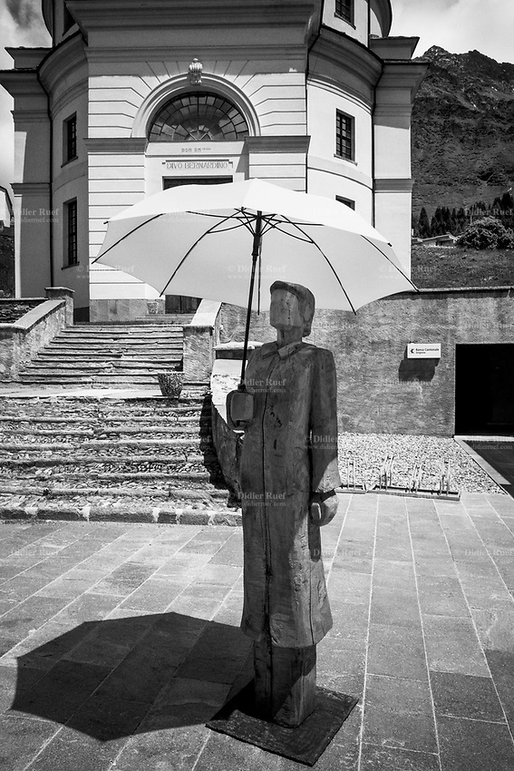 """Switzerland. Canton Graubunden. San Bernardino. Catholic church.  The wooden sculpture """"Hope"""" by artist Andreas Hofer is holding a green umbrella in her hand. The art work is a part of a tour organized by Greenhope Foundation (Sports against cancer). Hope embodies hope, passion, positivity and love. The sculpture thus characterizes the past, the present and, by its physical presence, will further determine the future of Greenhope. San Bernardino is a mountainous village.The church dates from around 1450. The village is part of the municipality of Mesocco. 21.06.2020 © 2020 Didier Ruef"""