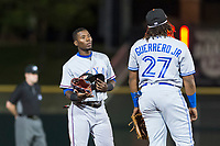 Surprise Saguaros left fielder Julio Pablo Martinez (40), of the Texas Rangers organization, talks to Vladimir Guerrero Jr. (27), of the Toronto Blue Jays organization, between innings of an Arizona Fall League game against the Scottsdale Scorpions at Scottsdale Stadium on October 15, 2018 in Scottsdale, Arizona. Surprise defeated Scottsdale 2-0. (Zachary Lucy/Four Seam Images)