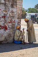 """Morocco.  Two Old Men Talking in the Shade,  Had Draa Market, Essaouira Province.  The seated man is making the Moroccan gesture for """"zero"""" or """"bad."""""""