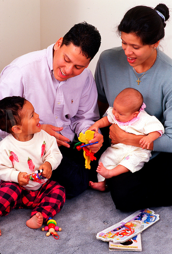A young Hispanic family (mother, father, and two small children) interacting.