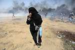 A Palestinian woman reacts from a tear gas canister fired by Israeli security forces during clashes in tents protest where Palestinians demanding the right to return to their homeland, at the Israel-Gaza border, in Khan Younis in the southern Gaza Strip, on May 11, 2018. Photo by Ashraf Amra