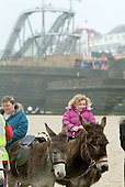 A young girl rides a donkey on the beach in the Yorkshire seaside resort of Bridlington on Easter Bank Holiday.