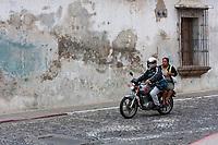 Antigua, Guatemala.  Couple on Motorbike, no Helmet on Passenger.