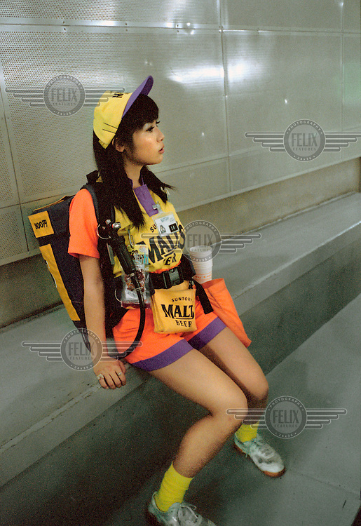 A beer hostess taking a break from handing out Suntory Malts beer at the Tokyo Dome stadium.