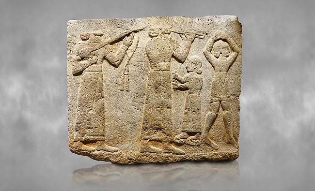 Hittite monumental relief sculpted orthostat stone panel of Procession. Limestone, Karkamıs, (Kargamıs), Carchemish (Karkemish), 900-700 B.C. Anatolian Civilisations Museum, Ankara, Turkey.<br /> <br /> Musicians. Two musicians with short arms, wearing long dresses and wide belts; one plays a Saz (a stringed musical instrument) with tassels on the handle while the other plays the flute. The third small figure holds castanets (?) in his hands. The figure on the right wears a short skirt, contrary to the others. She dances over her finger tips with her hands over her head.<br /> <br /> Against a grey art background.