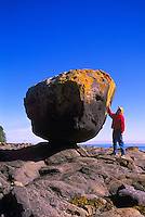 "Haida Gwaii (Queen Charlotte Islands), Northern BC, British Columbia, Canada - Woman standing beside ""Balance Rock"" at Low Tide, near Skidegate on Graham Island (Model Released)"
