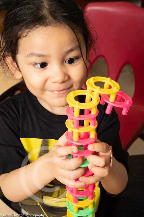 Education preschool 3-4 year olds boy holding construction he built from round colorful plastic stacking pieces, proud