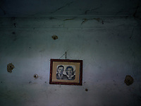 A portrait of a couple hangs from a wall in a war-damaged home in the village of Zolote. The village has largely been abandoned as residents flee fighting between Russian-backed separatists and the Ukrainian military.