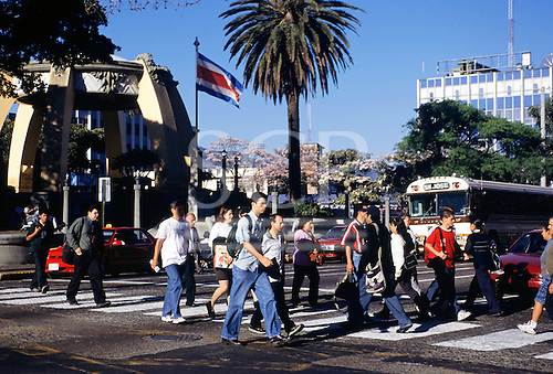 San Jose, Costa Rica. Pedestrians on a crossing in the Parque Central with the bandstand kiosk.