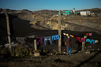 Cloths are hung out to dry along a fence which separates the Yanacancha neighborhood of Cerro de Pasco, Peru from the edge of the open-pit mine.