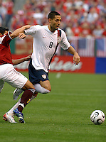 Clint Dempsey runs with the ball as a holds off a Venezuelan defender. USA (2) vs Venezuela (0) at Browns Stadium in Cleveland, Ohio, May 26, 2006.
