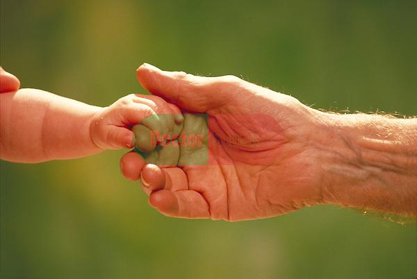 infant's hand holding elder's hand