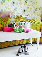 Colourful Christmas presents wrapped in Medusa paper and ribbons have been placed on the bench at the end of this bed