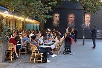 Europe/France /ile de FRance/Paris/75011: Terrasse de café Place Verte devant le Mur Oberkampf - Au coeur du XIe arrondissement parisien, le M.U.R. a mis en place le Mur Oberkampf qui emprunte à l'affichage publicitaire sa périodicité : 24 oeuvres se succèdent par an. Deux fois par mois, une nouvelle création recouvre la précédente. Oeuvre de Andrea Michaelsson alias Btoy une artiste espagnole qui présente 3 portraits  de Louise Michel  // Europe / France / ile de FRance / Paris / 75011: Place Verte café terrace in front of the Oberkampf Wall - In the heart of the 11th arrondissement in Paris, the M.U.R. has set up the Oberkampf Wall, which borrows its periodicity from advertising posters: 24 works follow one another per year. Twice a month, a new creation overlaps the previous one. Work of Andrea Michaelsson alias Btoy a Spanish artist who presents 3 portraits of Louise Michel