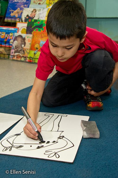 MR / Schenectady, New York. Paige Elementary School (urban public elementary school). First grade classroom. Student (boy, 6, Hispanic American) drawing a picture of a robot using dry erase board. MR: Era2. ID: AL-g1g. © Ellen B. Senisi.