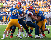 Pitt linebacker Quintin Wirginis (58) forces a fumble from Syracuse quarterback Eric Dungey resulting in a return for a Pitt touchdown. Also pictured is Pitt defensive lineman Shane Roy (93). The Pitt Panthers defeated the Syracuse Orange 44-37 in overtime at Heinz Field in Pittsburgh, Pennsylvania on October 6, 2018.