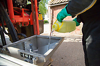 Pouring liquid chemical into the induction bowl of sprayer - Norfolk, May