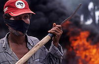Riot, burning of tires, rural workers of MST - Movimento Sem Terra ( Landless Workers Movement ) block road in Bahia State, northeastern Brazil, demonstration for land reform - activist holds a sickle and hides his face with a black mask.
