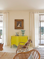 A bright yellow sideboard and a gilt-framed portrait sit between a pair of leaded French windows that are dressed with sheer cream curtains