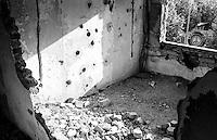 Mostar, un edificio in rovina, danneggiato durante la guerra. Fori di proiettile nel muro e un simbolo della pace all'esterno, --- Mostar, the ruin of a building damaged during the war. Bullet holes in the wall and a peace sign outside