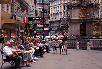 Vienna, Austria, Wien, People sitting on bench in the plaza on Graben Street in downtown Vienna.