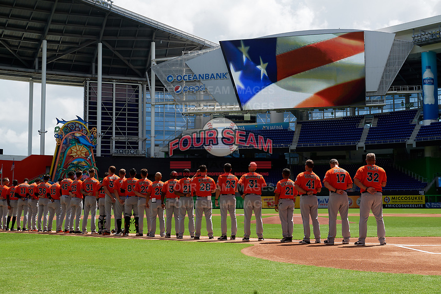 Miami Marlins players and coaches line up along the third baseline for the national anthem before a Florida Instructional League game against the Washington Nationals on September 26, 2018 at the Marlins Park in Miami, Florida.  (Mike Janes/Four Seam Images)