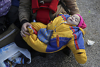 Pictured: A young baby is held by her migrant mother Friday 26 February 2016<br /> Re: Hundreds of refugees that crossed the border from Turkey to the Greek islands, have arrived at the port of Piraeus near Athens, Greece