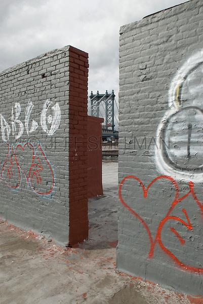 AVAILABLE FROM JEFF AS A FINE ART PRINT.<br /> <br /> AVAILABLE FROM JEFF FOR COMMERCIAL AND EDITORIAL LICENSING.<br /> <br /> Manhattan Bridge and Overcast Sky, Viewed from Behind a Graffiti Covered Brick Wall on a Rooftop in the DUMBO neighborhood of Brooklyn, New York City, New York State, USA