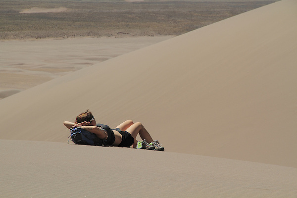 Woman resting in Great Sand Dunes National Park, Colorado John offers private photo trips to Great Sand Dunes National Park and all of Colorado. All year long.