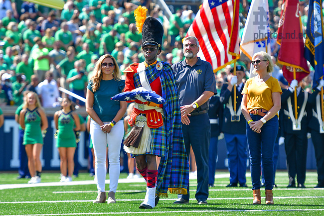 September 18, 2021; A member of the Irish Guard holds the U.S. flag presented by (l-r) Indiana Department of Health chief medical officer Dr. Lindsay Weaver, Indiana Governor Eric Holcomb and Indiana State Health Commissioner Dr. Kristina Box before the game against the Purdue Boilermakers. (photo by Matt Cashore/University of Notre Dame)
