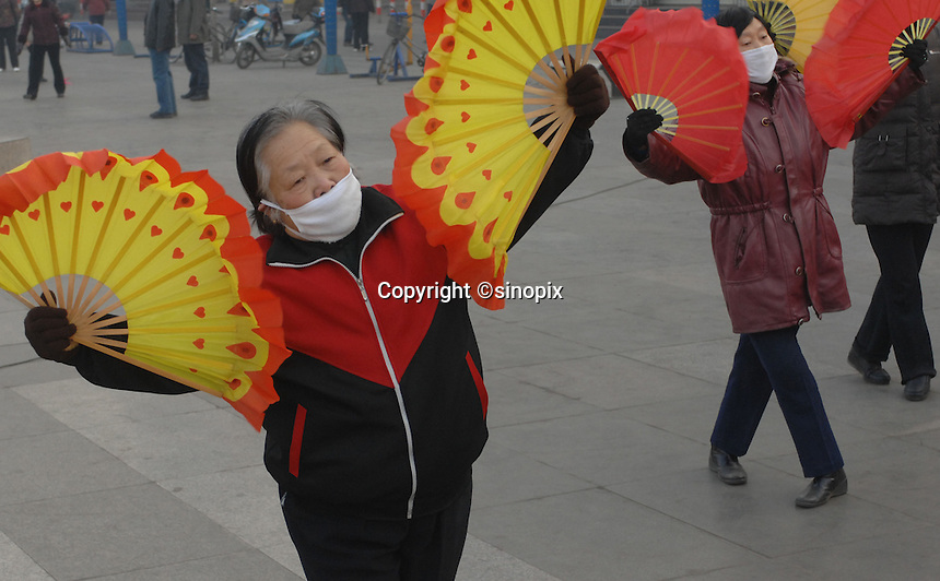 Ladies wear protective masks hile practising early morning fan dancing & Tai Chi in Linfen, Shanxi Province, China. Linfen has been identified as one of the most polluted cities in China..30 Jan 2007