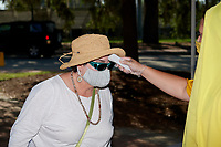 Fans get their temperatures taken while wearing a required protective mask before a Collegiate Summer League game  between the Macon Bacon and Savannah Bananas on July 15, 2020 at Grayson Stadium in Savannah, Georgia.  (Mike Janes/Four Seam Images)