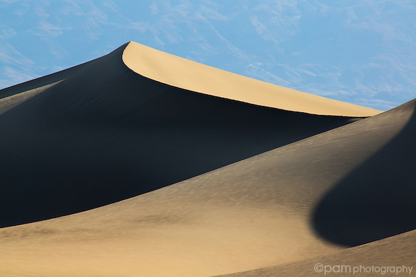 Sloping sand dune against blue mountain.  Taken at the Mesquite Dunes in Death Valley