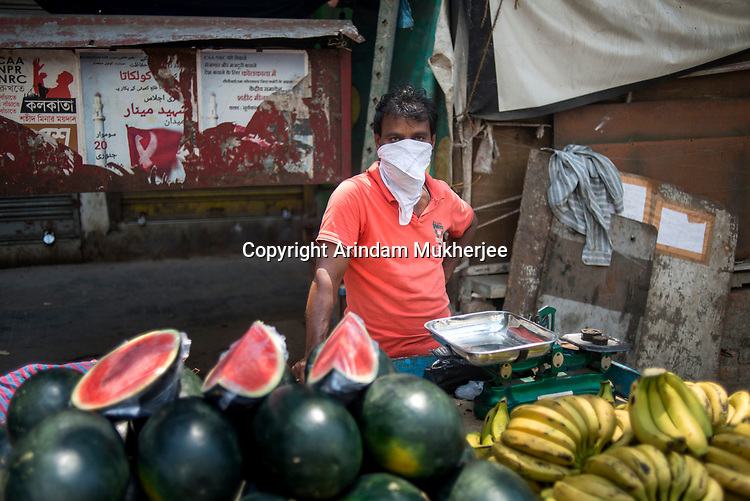 A man sells watermelon and bananas during the allowed hours of grocerry and vegetable sales during 21 days of lockdown in India due to corona virus pandemic. Kolkata, West Bengal, India. Arindam Mukherjee