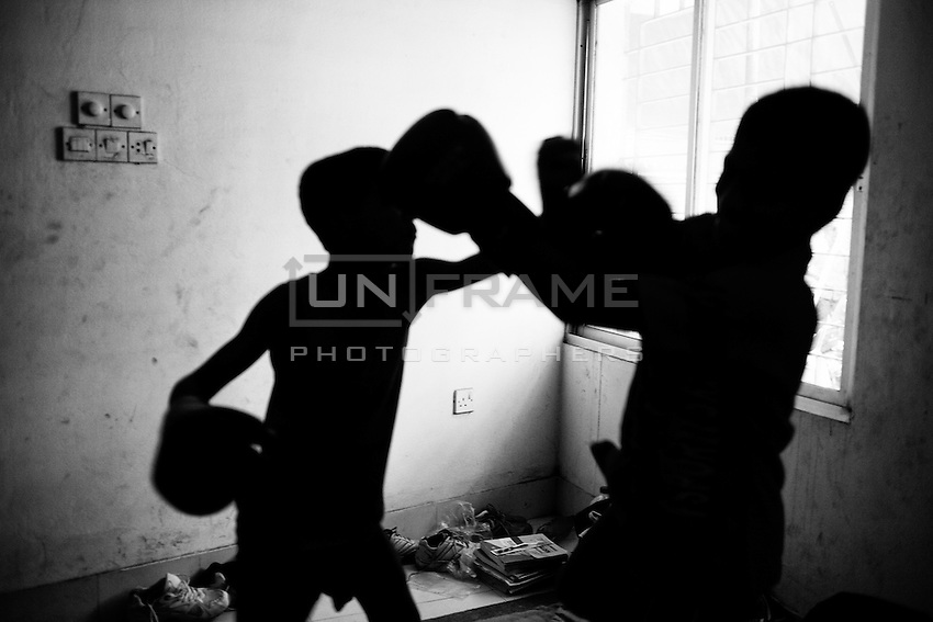 Two young boy fights with boxing gloves inside of their living place.