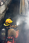 A firefighter spraying water on a structure fire hotspot