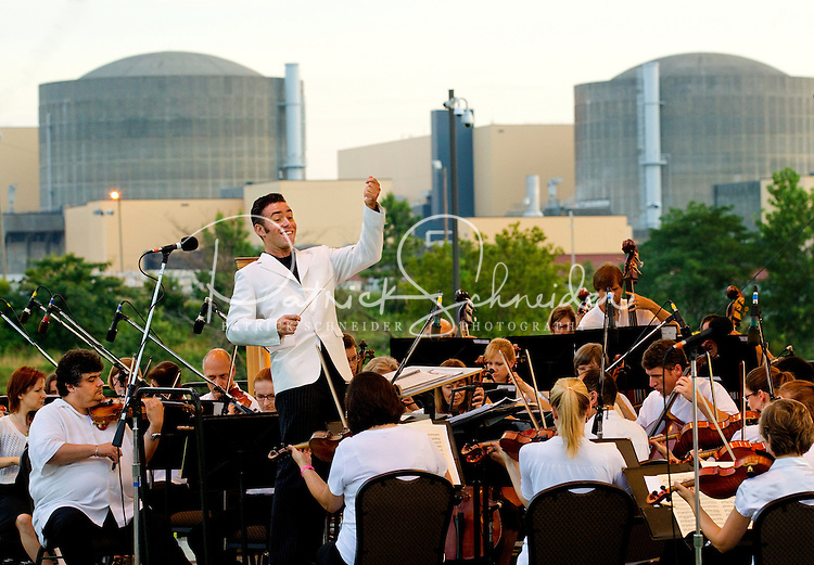 """Event photography of the Charlotte Symphony performing in a free outdoor concert June 17, 2012 at Duke Energy's McGuire Nuclear Station EnergyExplorium in Cornelius, NC. The symphony orchestra performed a """"musical travels"""" program. Albert George Schram conducted."""