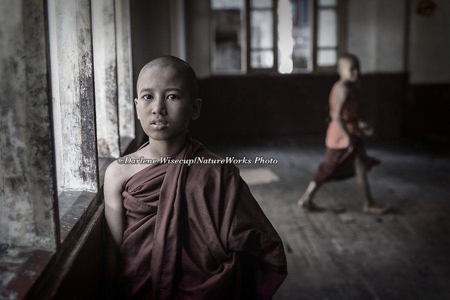 A young monk pauses for a portrait as another looks on in the background,  Kalaywa Taw Ya Monastery, Yangon, Myanmar