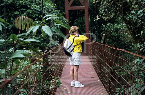 Monte Verde, Costa Rica. Tourist crossing a bridge above the forest at the Sky Trek ecotoursm attraction.