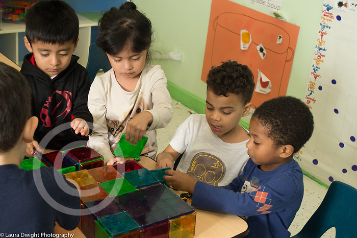 Preschool 3-4 year olds group of four chidren (3 boys and a girl) playing with magnetic blocks